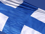 Close-up of the Flag of Finland on White Fabric with a Blue Cross Against Blue Sky Photographic Print