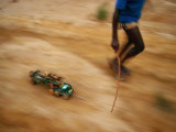 Child Pulling his Toy Truck at High Speed Photographic Print by Michael Nichols
