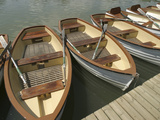 A Dock with Several Rowboats Lined up in the Water Photographic Print