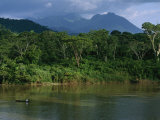 A Canoe Dwarfed by the El Almandro River and Surrounding Rain Forest Photographic Print by Stephen Alvarez