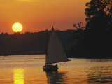 Gaff-Rigged Catboat Sails Along the Shoreline at Sunset Photographic Print by Skip Brown