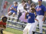 Boy Swinging a Baseball Bat on a Field Photographic Print