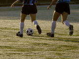 Low Section View of Two Female Soccer Players Kicking a Soccer Ball Photographic Print