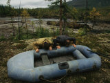 Two Men Use Lung Power to Top Off Their Inflatable Raft Photographic Print by Randy Olson