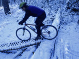 Man Mountain Biking in Snowy Forest Photographic Print