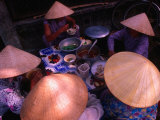 Women in Traditional Conical Hats Sitting Down to Meal at Market, Hoi An, Vietnam Photographic Print by John Banagan