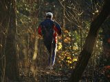 Jogger Running on Sun Dappled Trail Through Rock Creek Park Photographic Print by Raymond Gehman