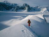 A Skier Moving Along a Ridge in Snow-Covered Mountains Photographic Print by Tim Laman