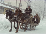 A Sleigh Serves as a Taxi on a Snow-Covered Village Street Photographic Print by Gordon Gahan