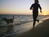 A Woman and Her Dog Run on the Beach at Sunset Photographic Print by Skip Brown