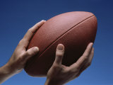 Hands Holding Football with Blue Background Photographic Print
