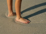 Feet in the Wet Sand of a Beach Wait for the Next Surge of Surf Photographic Print by Paul Damien