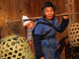Miao Woman with a Baby and Carrying Chicken Cages, Kaili, China Lámina fotográfica por Keren Su