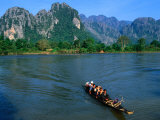 Longboat Crossing Nam Song from Limestone Formations with Honeycomb Caves, Vang Vieng, Laos Photographic Print by Kraig Lieb