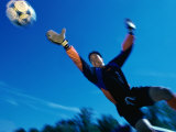 Low Angle View of a Teenage Goalie Reaching For The Ball Photographic Print