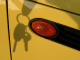 Shadow of Keys Against a Yellow Car Photographic Print