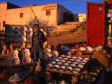 Boy Selling Ceramic Pottery from Roadside Stall, Tripoli, Libya Photographie par Patrick Syder
