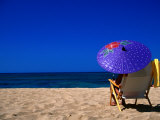 A Girl on the Beach Shading Under a Colourful Umbrella, Waikiki, Oahu, Hawaii, USA Photographic Print by Ann Cecil