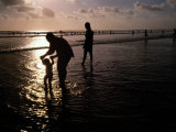 Families Play in a Shallow Lagoon at Sunset Photographic Print by Michael Nichols