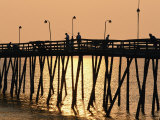 People on a Pier are Silhouetted at Twilight Photographic Print by Steve Winter