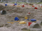 A Childs Colorful Toys are Scattered Throughout a Sand Box Photographic Print by Roy Gumpel