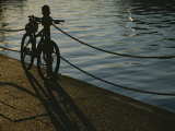 Bicycle Resting on a Railing Along Victoria Harbour as the Sun Sets Photographic Print by Todd Gipstein