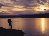 A Hiker Pauses for Reflection Alongside Lake Powell at Sunset Photographic Print by Gordon Wiltsie