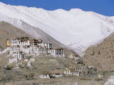 A Tibetan Temple is Built Atop a Hill with the Himalaya Mountains as a Backdrop Photographic Print by Monika Klum