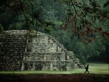 A Spider-Monkey Strolls Past a Small Pyramid Photographic Print by Kenneth Garrett