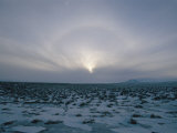 An Aurora Appears as the Sun Sets/Rises over a Snowy Field Photographic Print by Sisse Brimberg