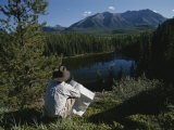 A Man with a Cowboy Hat Reads a Map and Gazes Across a River Photographic Print by Raymond Gehman