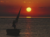 A Windsurfer Comes Near a Small Boat at Sunset Photographic Print by Bill Curtsinger