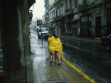 Two People Share a Raincoat as They Hurry Down a Rainy Street Fotodruck von Pablo Corral Vega