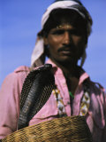 An Indian Snake Charmer Holds a Basket with a King Cobra in It Photographic Print by Ed George