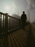 A Silhouetted Man Walks Towards an Industrial Area Photographic Print by Jodi Cobb