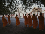 Buddhist Monks in Orange Robes Stand Outside an Ornate Building Photographic Print by Jodi Cobb