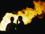 Natural Gas Workers Silhouetted by Burning Dross Photographic Print by George F. Mobley