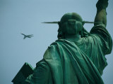 An Airplane Flies Near the Statue of Liberty Photographic Print by Joel Sartore