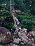 People Crossing Sagging Suspension Bridge Over Khudi Khola on Annapurna Circuit, Nepal Photographie par Tony Wheeler