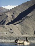 A Boatman Rows a Yak Skin Boat Across the Lhasa River Photographic Print by Gordon Wiltsie