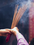 Worshipper Burning Incense in the Wong Tai Sin Temple, Kowloon, China Photographic Print by Michael Coyne