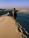 Woman Walking Towards Car on Sand Dune Ridge, Khor Al-Adaid, Qatar Photographic Print by Mark Daffey