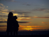 Sisters Silhouetted by Sunset Photographic Print by Angelo Cavalli