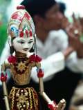 Traditional Puppet with Vendor in Background, Jakarta, Indonesia Photographic Print by Nicholas Pavloff