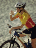 Young Woman Drinking Water While Sitting on a Bicycle Photographic Print