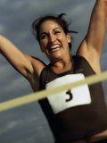 Low Angle View of a Female Athlete with Arms Raised Photographic Print