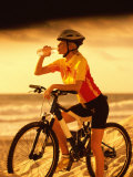 Young Woman Drinking Water Sitting on a Bicycle Photographic Print