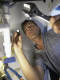 Low Angle View of a Young Man Checking the Plumbing with a Flashlight Photographie