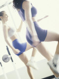 Two Young Women Exercising in a Health Club Photographic Print