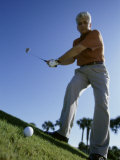 Low Angle View of a Senior Man Swinging a Golf Club Photographic Print